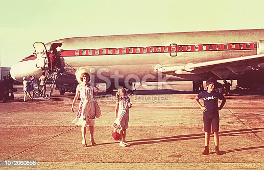 istock Vintage photo of a family boarding an airplane 1072060856
