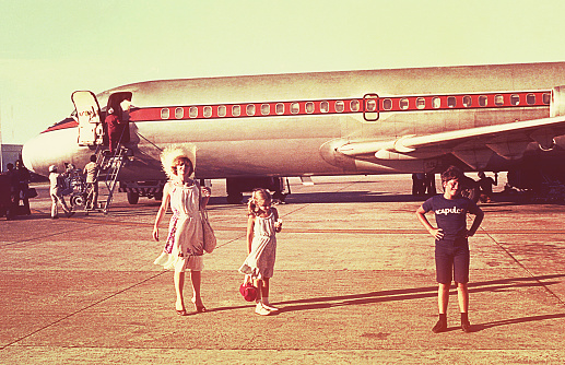 Vintage image of a mother and her children before boarding an airplane on a summer vacation.
