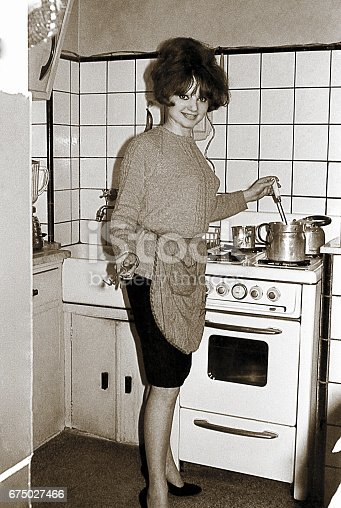 Vintage black and white photo from the sixties featuring a young woman cooking in the kitchen