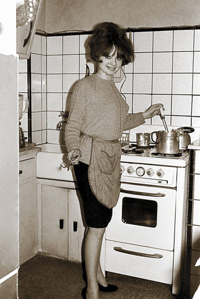 vintage photo of a young woman in the kitchen - archival stock photos and pictures