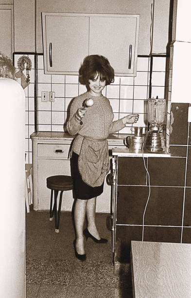 Vintage photo of a young woman in the kitchen Vintage black and white photo from the sixties featuring a young woman cooking in the kitchen cooking black and white stock pictures, royalty-free photos & images