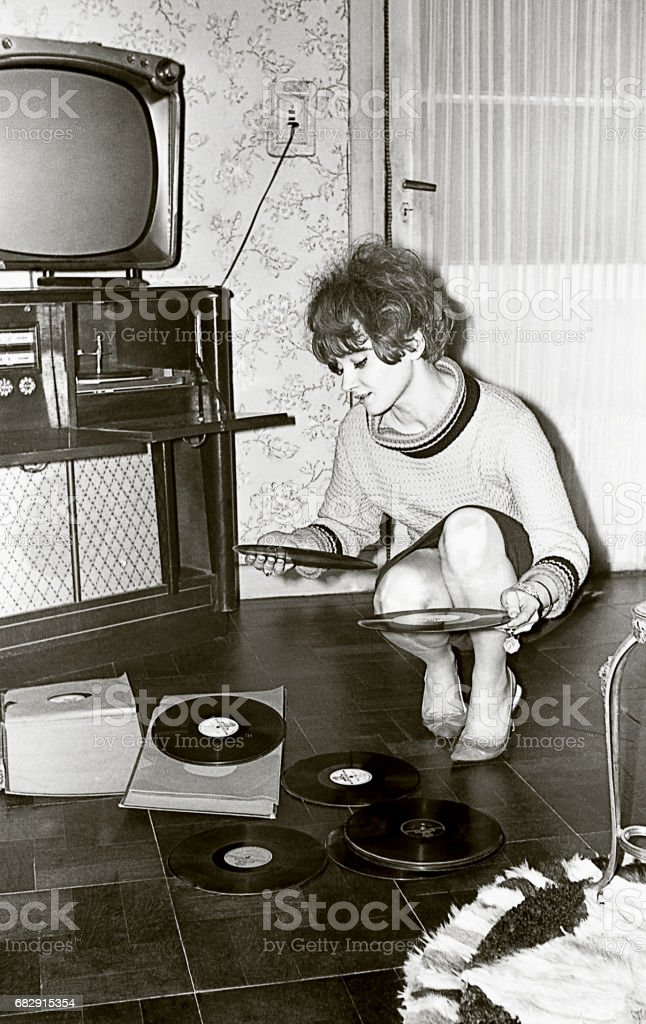 Vintage Photo of a young woman looking at vinyl records​​​ foto
