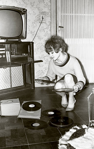 vintage photo of a young woman looking at vinyl records - archival stock photos and pictures