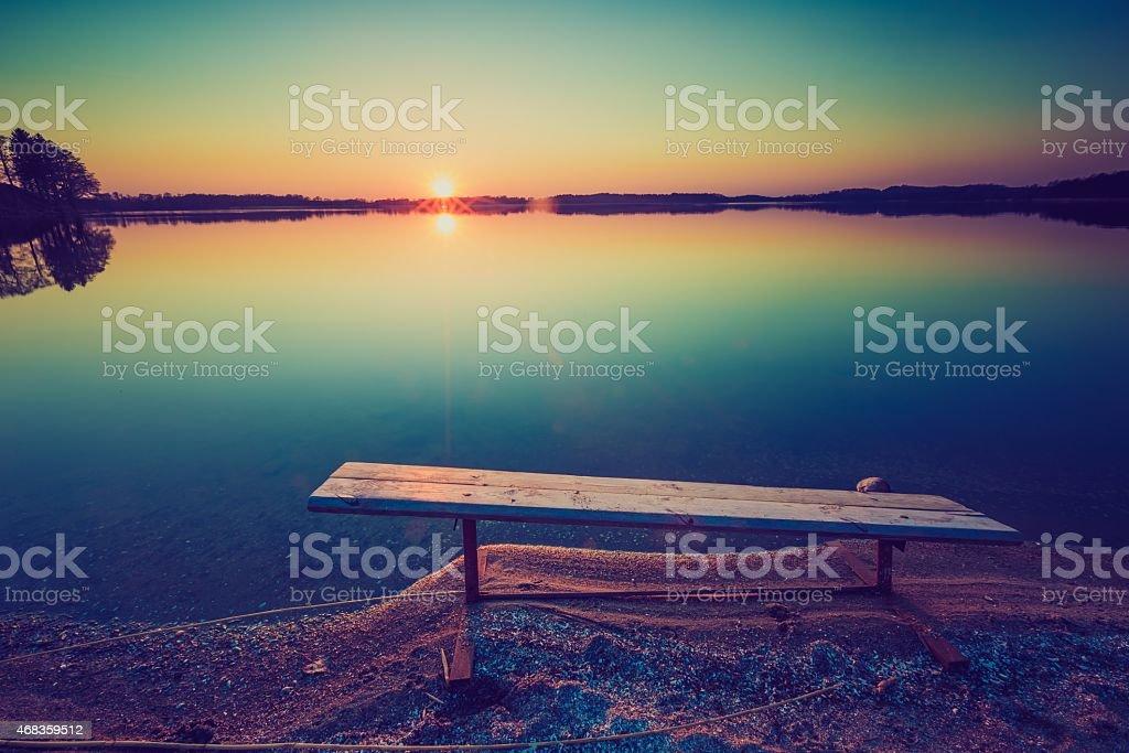 Vintage photo of bench on lake shore at sunset royalty-free stock photo