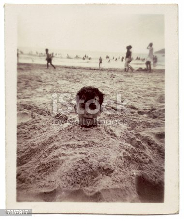 Head poking out from the sand.  Image taken in 1957.  Note that the image has soft focus and grain and grunge because of its age