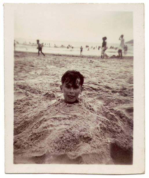 vintage photo of boy buried in sand at the beach - 懷舊色調 個照片及圖片檔