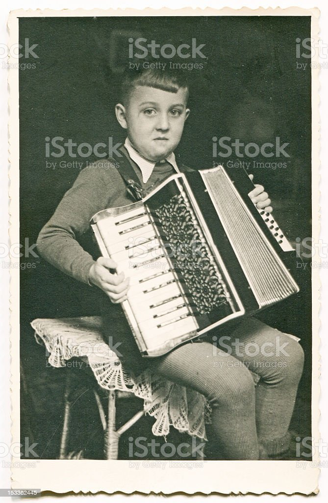 Vintage photo of boy playing an accordion stock photo