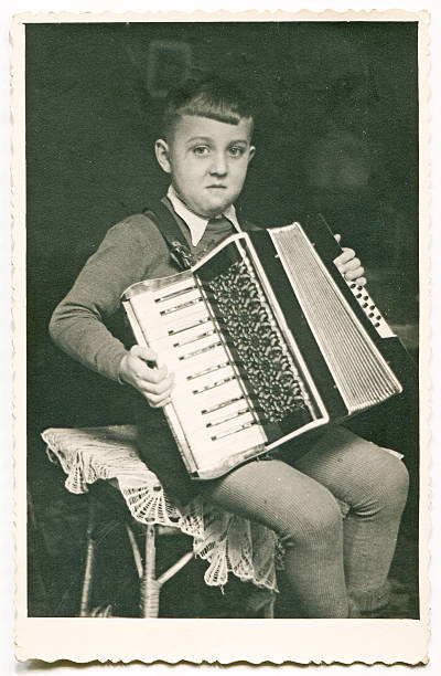 vintage photo of boy playing an accordion - accordion stock photos and pictures