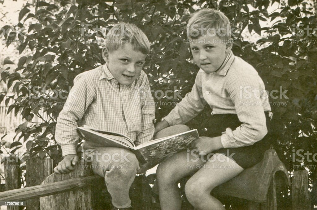 Vintage photo of brothers reading stock photo
