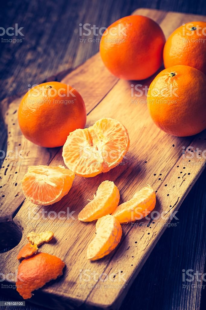 Vintage photo of fresh tangerines on wooden cutting board stock photo
