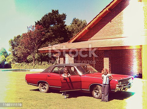 Vintage photo of children posing beside playing around a big vintage car.