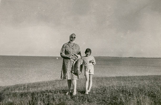 vintage photo of mother and daughter on beach - 1950s style stock photos and pictures