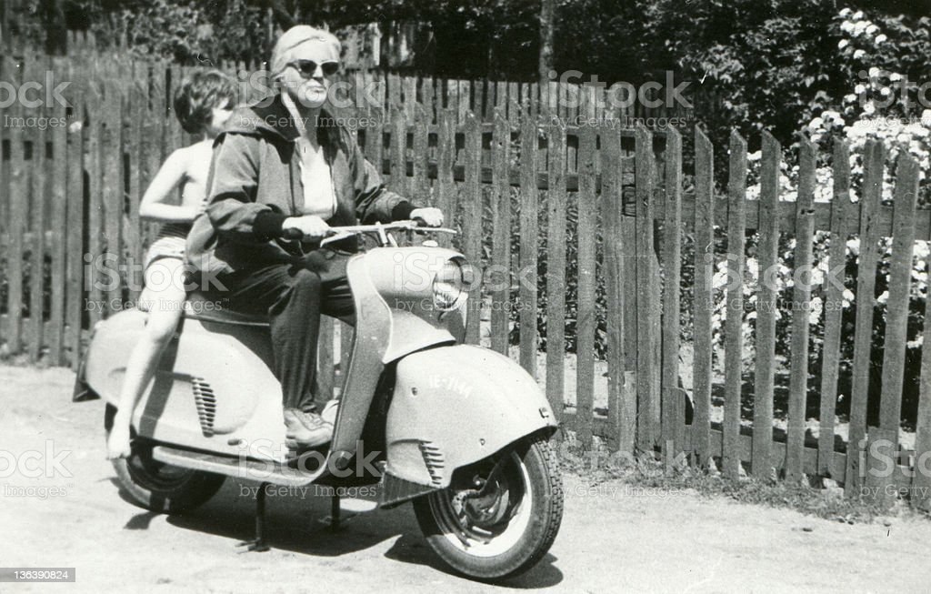 Vintage photo of mother and daughter on scooter stock photo
