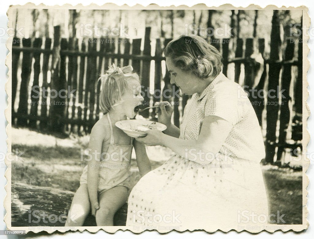Vintage photo of mother feeding her daughter stock photo