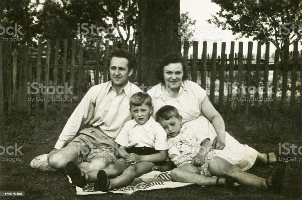 Vintage photo of parents with sons in garden stock photo
