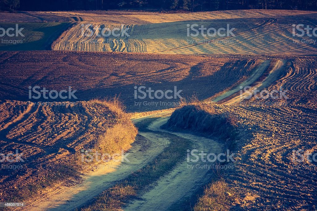 Vintage photo of sandy rural road and plowed fields royalty-free stock photo