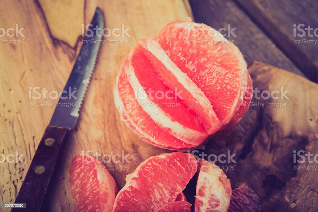 Vintage photo of sliced grapefruit on kitchen cutting board stock photo