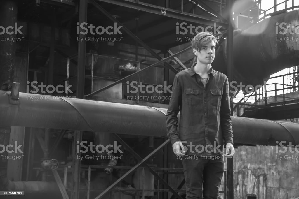 Vintage photo of teenage boy in industrial area stock photo