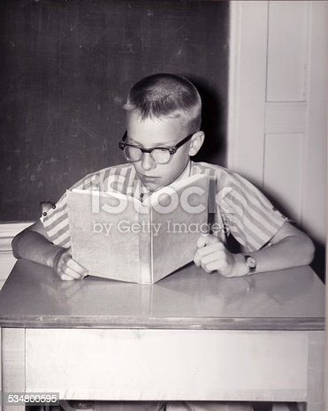 Vintage photograph of young boy reading a book at a desk in a school classroom