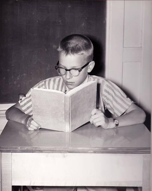vintage photo of young boy reading book - 1950s style stock photos and pictures