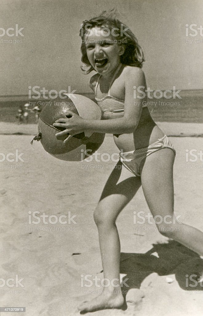 Vintage photo of young girl with a ball on beach stock photo