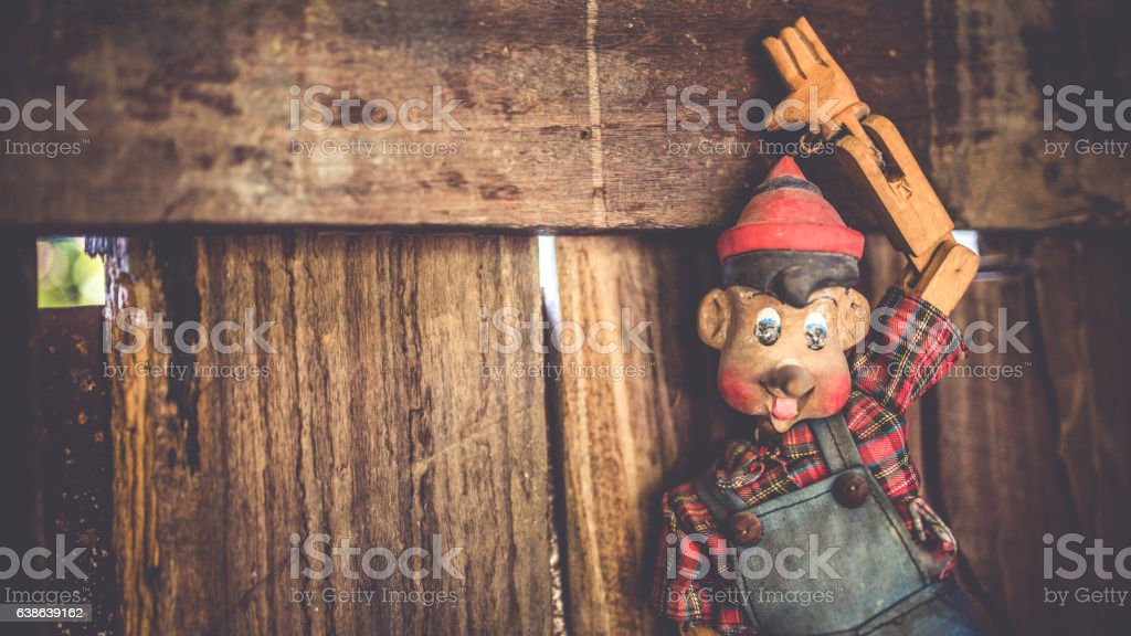 Vintage Photo Vintage pinocchio puppet doll on the old grunge wooden wall in horizontal picture. Adult Stock Photo