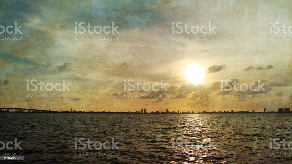 Vintage Photograph of a Sunrise Over the City Skyline with Clouds stock photo