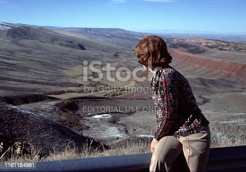 Wyoming, United States - January 01, 1976:  Vintage, authentic archival photograph of woman looking at a canyon in Wyoming, United States, 1976.