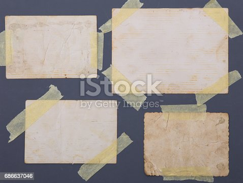 istock vintage photos taped on grey background 686637046