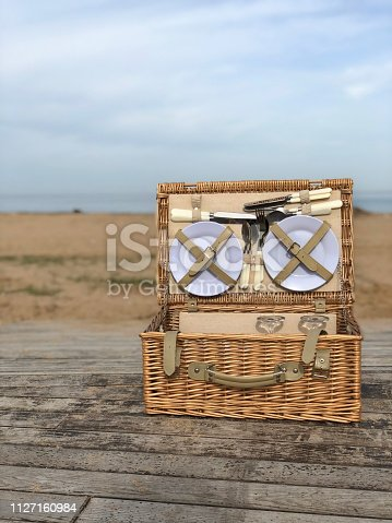 Traditional wicker vintage picnic basket with cutlery on wooden table by the seaside