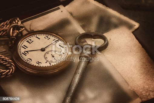 Vintage still life with old clock, key, book, pendant,  postcards lying on the table,