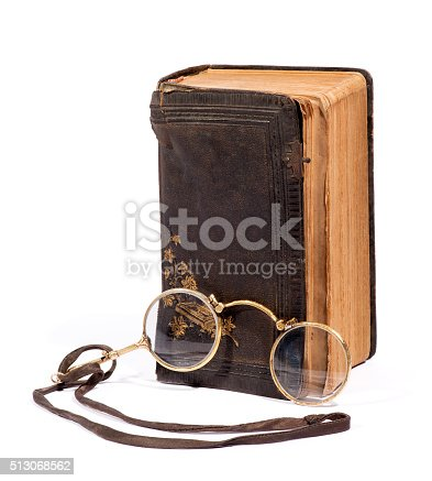 istock Vintage pince-nez glasses with an old book 513068562