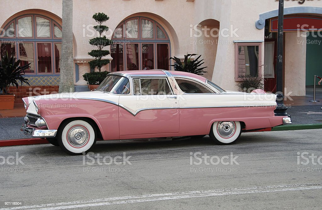Vintage pink and white car parked on street stock photo