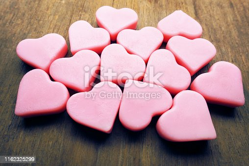 istock Vintage pink hearts grouping on wood table, love concept. 1162325299