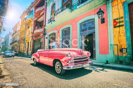 Vintage pink oldtimer car driving through Old Havana Cuba