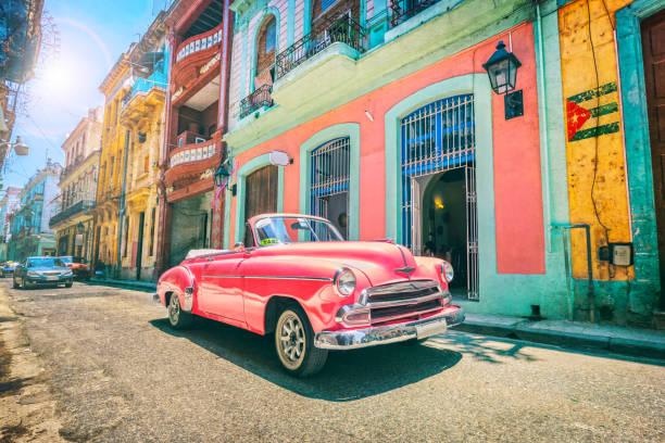 Vintage pink oldtimer car driving through Old Havana Cuba stock photo