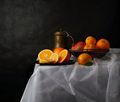 Still life with an old jug and a vase of fruit on a white tablecloth and a dark background in the style of old Dutch artists