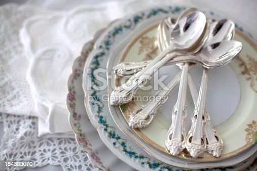 A stack of vintage floral plates with silver teaspoons on a table near lace doilies.
