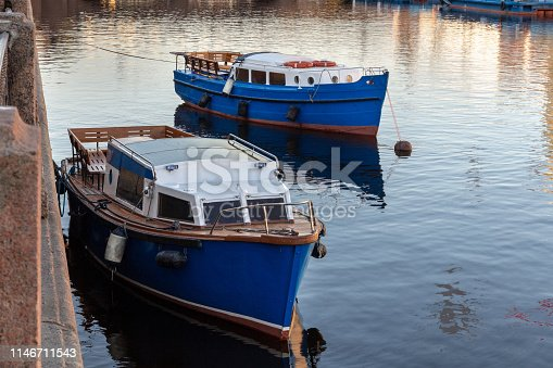 moored vintage pleasure boats at the granite wall of the river channel