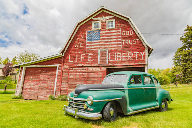 Vintage Plymouth Super De Luxe automobile and a weathered red a barn. stock photo