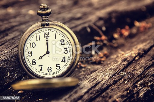 istock vintage pocket watch on grunge wood log 533978068