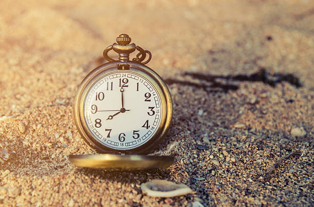 vintage pocket watch on sand beach background - desolated stock pictures, royalty-free photos & images