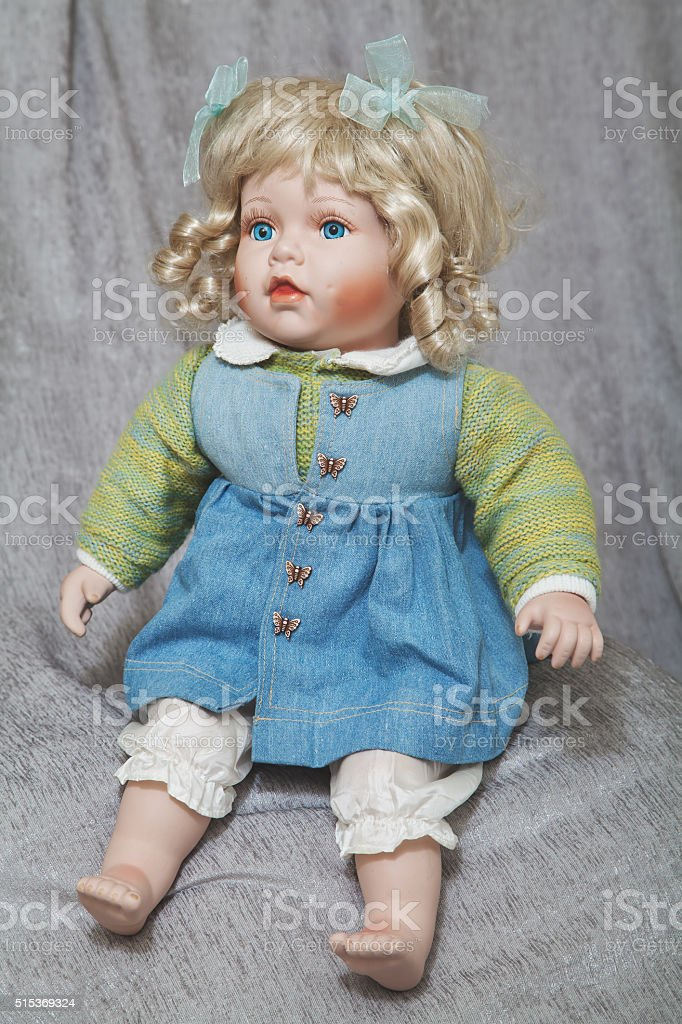 Vintage porcelain doll blonde on gray fabric background stock photo