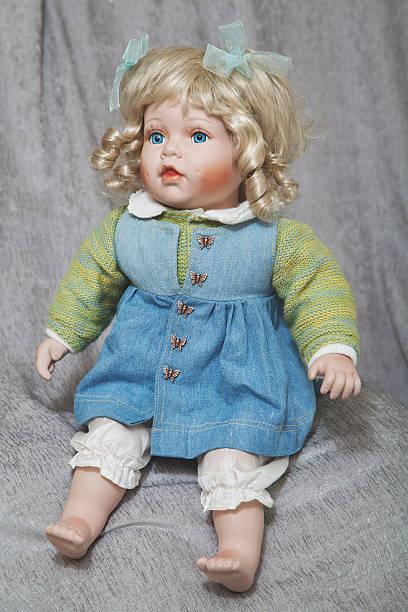 vintage marioneta de porcelana rubia sobre fondo de tela gris - muñeca bisque fotografías e imágenes de stock