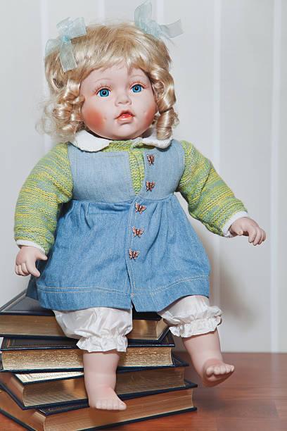 vintage rubia muñeca de porcelana, sentado en el montón de libros - muñeca bisque fotografías e imágenes de stock