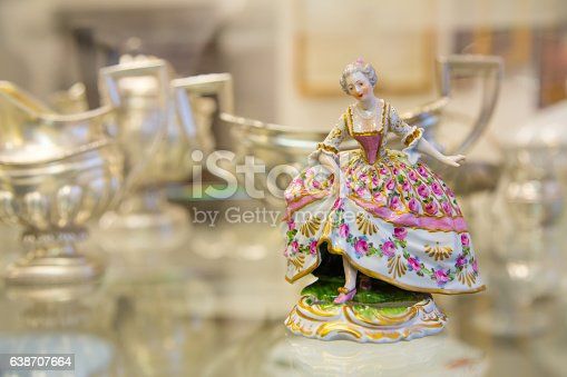 Color vintage porcelain doll in the blurry background. The doll depicts a medieval lady in a ball gown. Porcelain doll in vintage interior.