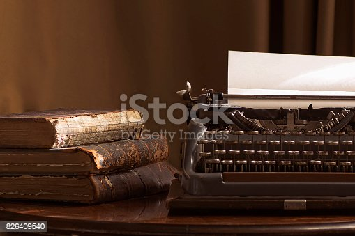 istock Vintage portable typewriter with a piece of paper and vintage books on a table 826409540