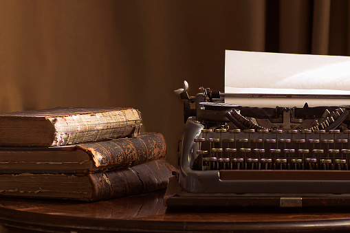 Vintage portable typewriter with a piece of paper and vintage books on a table