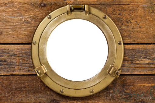 old brass porthole in wooden wall, window isolated with clipping path