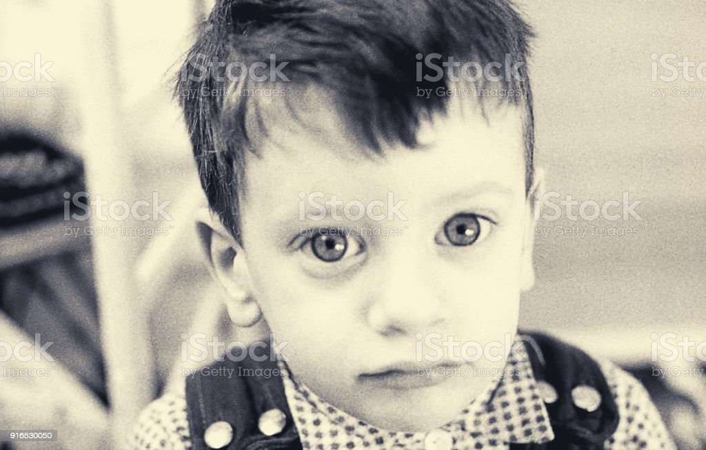 Vintage portrait of a toddler looking close at camera stock photo